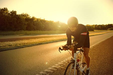 Licht von Fackeln von steigenden oder Sonne auf der Straße Fahrrad allein über asphaltierte Straße im Sommer über den Menschen Ausbildung Einstellung Standard-Bild
