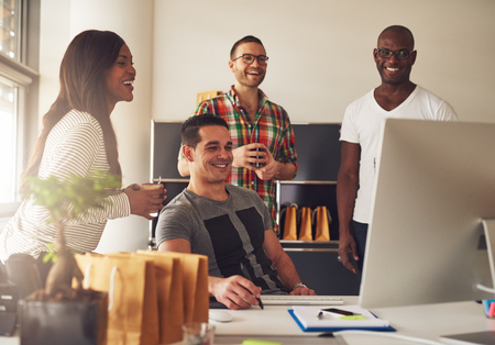 Diverse group of four Black, Hispanic and Caucasian young adult entrepreneurs together in front of computer monitor on desk at small business office