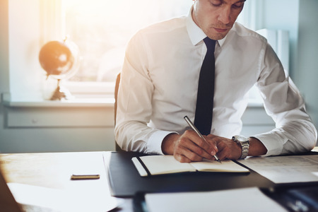 paralegal: Close up of business man in shirt and tie working in his office writing in a classic note book Stock Photo