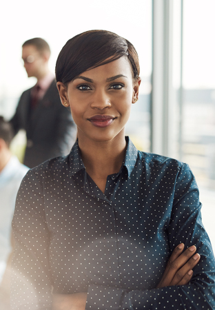 strong light: Beautiful young grinning business woman in office with polka dot blouse, folded arms and confident expression as strong light flare shines in front of her Stock Photo