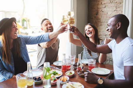 casual: Group of diverse male and female laughing young adults putting their drinking glasses together at table in restaurant with large window