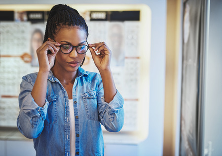 eye wear: Single beautiful young African-American woman in blue shirt testing the fit for eyeglasses on her head in eye wear shop Stock Photo