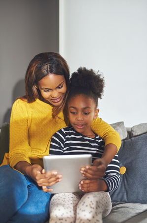 family couch: Little black girl and mom with tablet sitting in sofa smiling Stock Photo