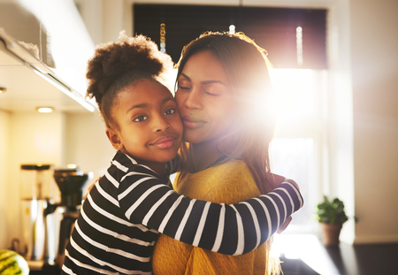 Loving child hugging mother looking at camera looking calm Stock Photo