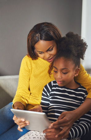 family couch: Afro american woman and child with tablet sitting in a sofa Stock Photo