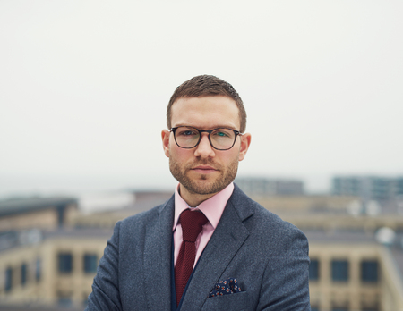 Determined intense young businessman wearing glasses standing on an outdoor patio of a high rise building staring at the camera with a serious expression