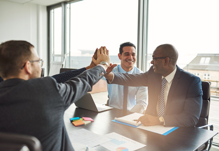 Successful multiethnic business team congratulating each other on an achievement giving a high fives gesture with their hands Stock Photo