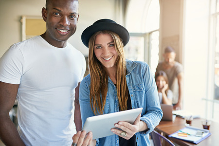 hispanic woman: Smiling young multiracial business team with a handsome African man and Hispanic woman standing having a discussion while holding a tablet computer