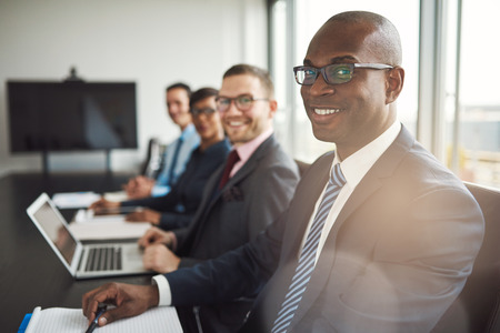 affiliates: Smiling confident African businessman in a meeting with a group of multiracial co-workers seated at a conference table in the office
