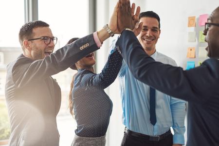 그들은 웃음과 그들의 성공을 응원으로 높은 끗 제스처를주고 행복 성공적인 다민족 비즈니스 팀