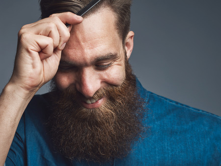 Well groomed handsome bearded man in blue denim shirt and happy expression combing his hair over gray background