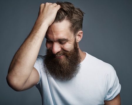 Laughing young man with long beard and white shirt holding hair while facing downward over gray background Stock Photo