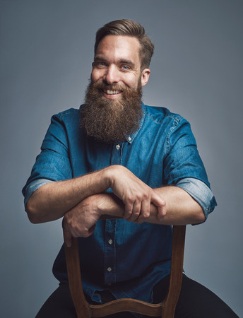 Cheerful laughing young bearded man wearing blue denim shirt with rolled up sleeves and arms on back of chair over gray background Stock Photo