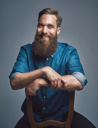 hombre con barba: Risa alegre joven con barba que usa la camisa de mezclilla azul con las mangas enrolladas y los brazos en la espalda de la silla sobre fondo gris