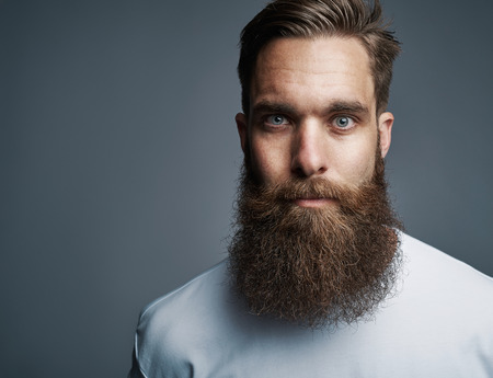 Close up on single serious handsome young Caucasian man with muscular build and well groomed beard over gray background