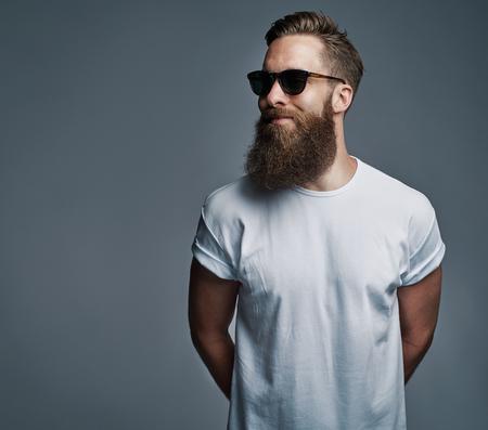 Portret van knappe enkele bebaarde jonge man met seus meningsuiting draagt een zonnebril en witte korte mouw shirt kijken over de grijze achtergrond met kopie ruimte