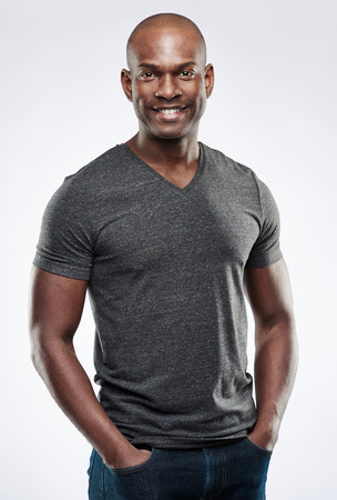 shaved head: Single handsome fit smiling young Black adult with shaved head and hands in jeans pants pockets over gray background