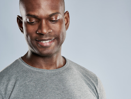 shaved head: Close up on single attractive grinning Black man with shaved head in gray shirt looking downward over background with copy space