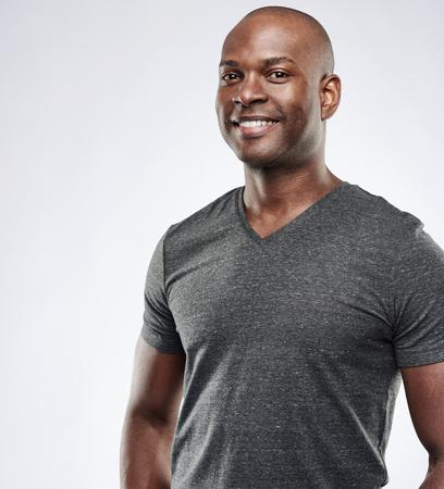 Singolo giovane fiero uomo africano muscolare in camicia grigia breve compressione manica su sfondo con spazio di copia