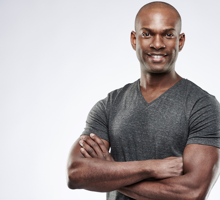 isolated man: Single handsome fit grinning young Black adult with shaved head and folded muscular arms over gray background with copy space