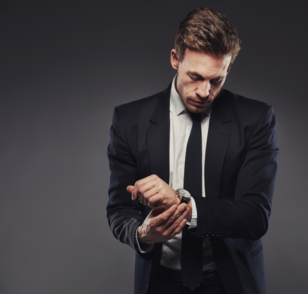 man style: Handsome young businessman in a black suit checking the time on his watch, standing against a gray background