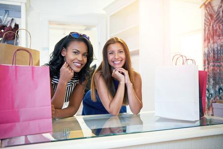 カメラに向かって笑みを浮かべてカウンターに寄りかかってストア内の衣料品購入のための支払いを待っている 2 つの幸せな若い女性 写真素材