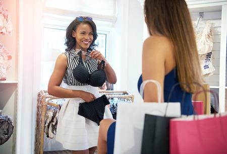 Dwie młode kobiety zakupy ubrania w butiku moda trzyma się stanik i majtki z uśmiechem