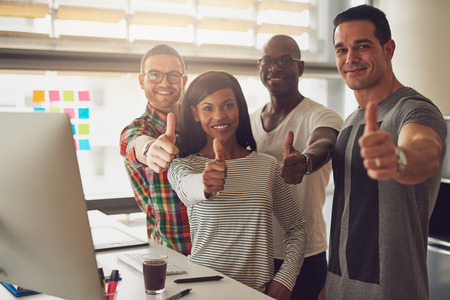 Diverse group of four business partners or entrepreneurs holding their thumbs up in approval or to like something in their office Фото со стока