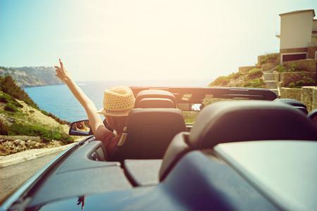 海に向かって手で帽子ジェスチャーでドライバーとしてコンバーチブル トップ自動車後部トランク エリアからの眺め