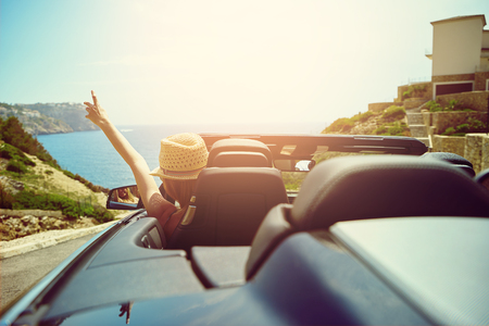 touring car: View from rear trunk area of convertible top automobile as driver with hat gestures with hand toward ocean