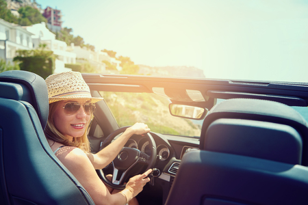 automobile: Beautiful young woman with hat and sunglasses in convertible top automobile looking back toward passenger seats