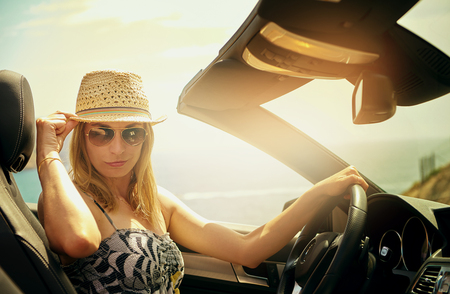Smirking young woman in sunglasses holding the brim of her straw hat while driving her luxury retractable roof automobile in bright sunlight photo