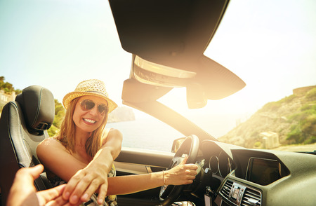 Happy young adult blond woman with hat and sunglasses in convertible top automobile reaching out to touch hand of passenger while driving or parked photo