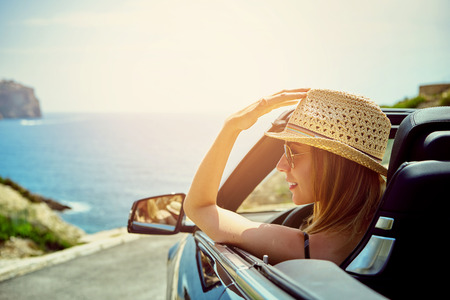 Mooie blonde lachende jonge vrouw met een hoed en zonnebril in cabriokap auto op zoek zijwaarts, terwijl geparkeerd in de buurt zee aan het water
