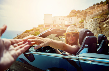 First person view on hand reaching for beautiful young woman with hat and sunglasses at the steering wheel of a parked convertible top automobile photo