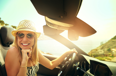 Cute grinning young woman in hat and sunglasses driving convertible car in bright sunlight photo