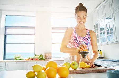 그녀의 부엌에서 수동 과즙을 사용하여 신선한 과일의 구색에서 건강한 과일 주스를 준비하는 젊은 웃는 여자에 맞게 높은 키 창 배경에 공간을 복사