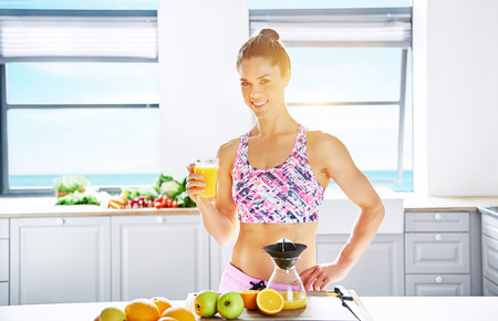 blend: Healthy diet and lifestyle concept with a fit attractive young woman with a lovely smile making fresh juice for assorted organic fruit in a clean bright kitchen with copy space