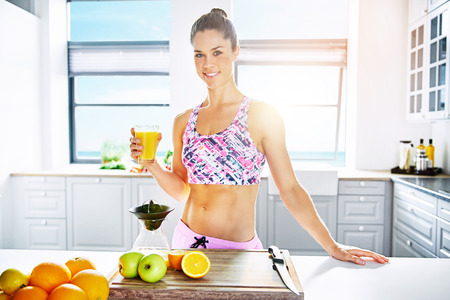 Health, fitness and diet concept with a shapely young woman standing holding a glass of freshly prepared juice from assorted fruit in a clean bright kitchen with copy space