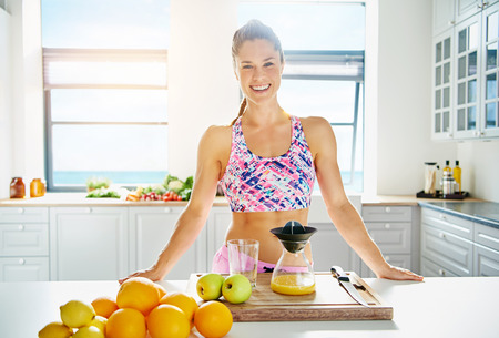 vivacious: Beautiful vivacious woman preparing fruit juice from fresh ingredients in her kitchen in a healthy diet and lifestyle concept