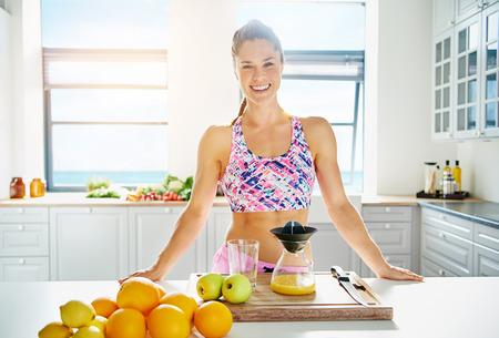 jugo de frutas: Hermosa mujer vivaz preparar zumo a base de ingredientes frescos en su cocina en una dieta y estilo de vida sano concepto Foto de archivo