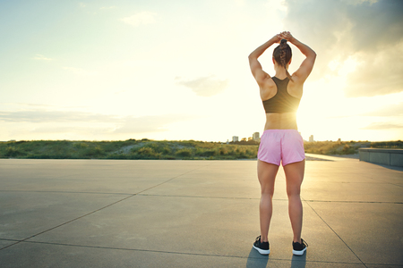 Fit muscular young woman standing on a rural road facing the rising sun doing stretching exercises with her arms raised above her head, with copy space