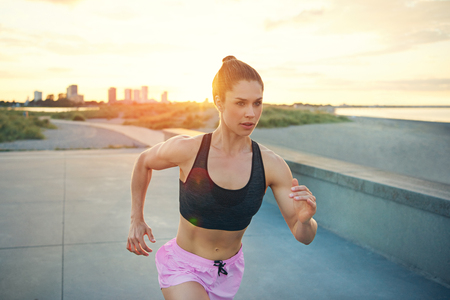 Sporty strong healthy young woman out jogging or running on a waterfront promenade at sunrise in an active lifestyle concept Stock Photo