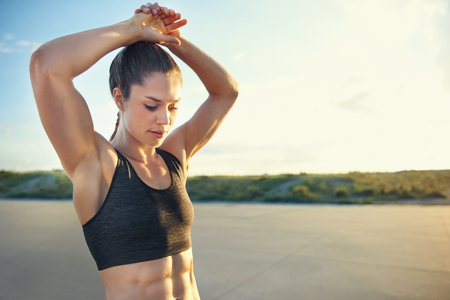 Fit young woman with toned abdominal muscles doing warming up exercises before a workout raising her arms above her head, rural road with copy space Stock Photo