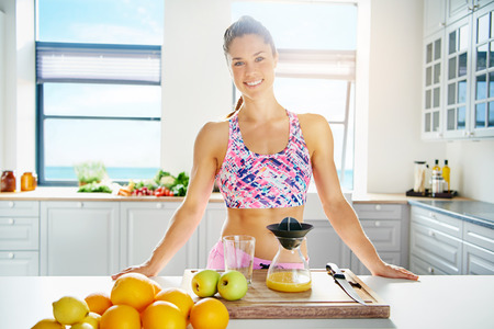 Fit healthy young woman with a lovely smile standing in her kitchen preparing fruit juice form a selection of fresh fruit on the counter Stock Photo