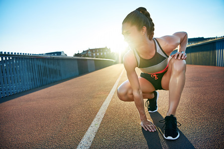 Sun highlights kneeling female jogger as she places one hand on the pavement