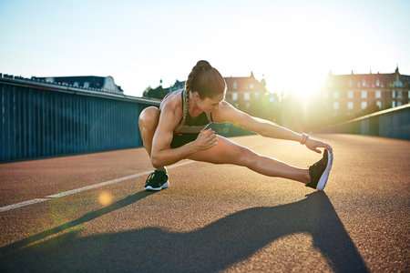 limbering: Sun highlights young muscular female athlete as she stretches preparing to run