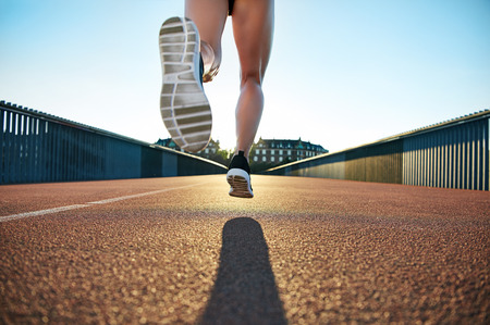 bounds: Bare legged jogger bounds towards apartments down empty road under a clear blue sky Stock Photo