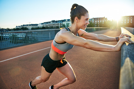 limbering: Woman stretches her legs by pressing against bridge by pressing against bridge