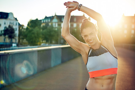 suppleness: Female athlete smiles at camera and stretches by raising both arms overhead and leaning to one side
